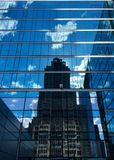 Office building with Windows reflecting the skyline of the city and blue sky behind it Royalty Free Stock Photos