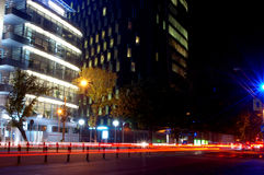 Office buildings. View of a corporate building at night. Trail lights in the street, slow shutter speed was used Stock Images
