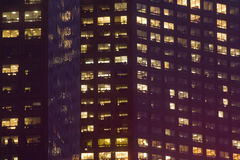 Office Buildings at Night. Two adjoining office buildings show all kinds of work going on even after dark royalty free stock image