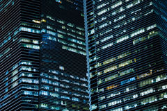 Office buildings in the night. Bright lights of the office skyscrappers in the dark Royalty Free Stock Photo