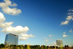 Office buildings and open field. Two modern office buildings with an open field, taken from a low perspective. Blue sky and little white clouds. Taken in Houston stock image