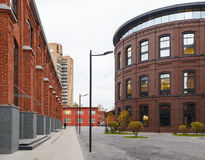 Office buildings. Red brick buildings of former factory, gasholders. Evening lighting, street lamps Stock Photo