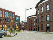 Office buildings. Red brick buildings of former factory, gasholders. Evening lighting, street lamps Stock Images