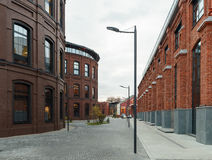 Office buildings. Red brick buildings of former factory, gasholders. Evening lighting, street lamps Royalty Free Stock Images