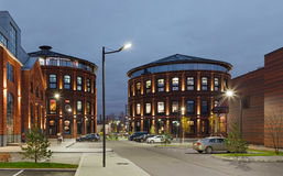 Office buildings. Red brick buildings of former factory, gasholders. Evening lighting, street lamps Stock Photos