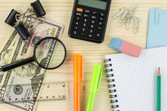 Office, business tools with blank notebook and dollars on wooden table Royalty Free Stock Image