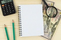 Office, business tools with blank notebook and dollars on wooden table Stock Photo