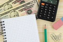 Office, business tools with dollars and calculator on wooden table Stock Photos