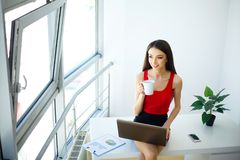 Office Business Woman Works on the Computer. Light Modern Office. Dressed in Red Sweater and Black Skirt. Sits on the Table and Ho. Office. Business Woman Works Royalty Free Stock Images