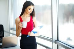 Office Business Woman Works on the Computer. Light Modern Office. Dressed in Red Sweater and Black Skirt. Sits on the Table and Ho. Office. Business Woman Works Royalty Free Stock Photo