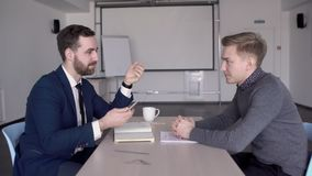 In office businessman interviews a young jobseeker at a table. Man in a suit and with a beard asks questions in front of a male employee to identify abilities stock footage