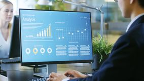 In the Office Businesswoman at Her Desk, She`s Using Personal Co. Mputer with Statistical Information Showing on It`s Screen. Her Colleague Sets Opposite to Her stock photography