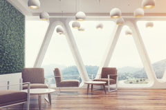Office cafe, grass wall, brown toned. Office cafe interior with a large grass wall, panoramic windows with triangular frames, white round tables and soft brown Royalty Free Stock Photo