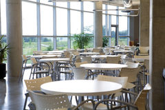 Office cafeteria with centered table. Office cafeteria in a modern clean building with centered table in focus Royalty Free Stock Images