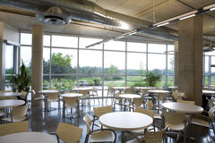 Office cafeteria view in modern building. Office cafeteria in a modern clean building with tables being naturally framed by concrete pillars. Shows a spacious Stock Images
