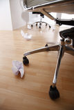 Office chair and crumpled paper on floor Royalty Free Stock Images