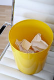 Office chair, dust bin and crumpled paper Royalty Free Stock Photography