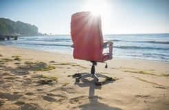 Office chair on sunny beach. Old office chair on the beach against the sun light royalty free stock photos