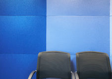 Office chairs against blue wall Stock Images