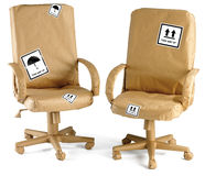 Office chairs all wrapped up in brown paper for a Stock Images