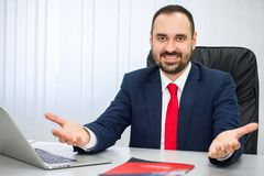 Cheerful man in a suit with a red tie invites to cooperate. In the office a cheerful man in a suit with a red tie invites to cooperate stock image