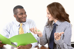 Office chit-chat. Pair of workers enjoy social conversation at work desk royalty free stock photo