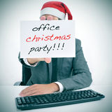 Office christmas party. A man sitting in his desk with a santa hat holding a signboard with the text office christmas party written in it Stock Photography