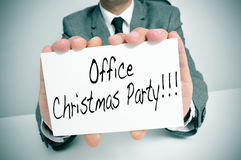 Office christmas party. A man wearing a suit sitting in a desk holding a signboard with the text office christmas party written in it Stock Photography