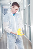 Office cleaner man putting rubber glowes. Man cleaning office wearing protective overalls royalty free stock images