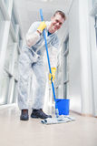 Office cleaning in overalls. Man cleaning office wearing protective overalls Royalty Free Stock Image