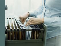 Office clerk searching files in the filing cabinet stock images