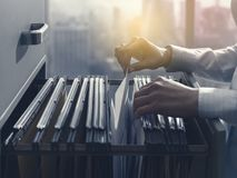 Free Office Clerk Searching Files In The Filing Cabinet Stock Photos - 141852843