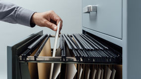 Office clerk searching for files. Into a filing cabinet drawer close up, business administration and data storage concept stock photography
