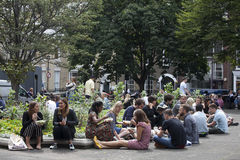 Office clerks sit on the grass and dine at Golden Square, Soho, exposing faces to the sun Stock Images