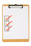 Office Clip Board. Cork clipboard holding blank paper that has three square boxes checked off with a red marker. Isolated on white Stock Photography