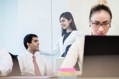 Office co-workers talking gossip behind back of businesswoman Royalty Free Stock Image