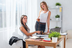 Office coffee break with two smiling female colleagues. Royalty Free Stock Photos