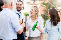 Office colleagues drinking beer after work Stock Photo