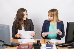 Office colleagues girl at a desk browsing documents. Two young beautiful girls colleagues sitting at the same desk in the office Royalty Free Stock Images
