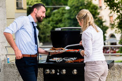 Office colleagues grilling sausages at bbq after work Stock Photo