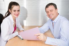 Office colleagues together look at a working folder at office desk. Two office colleagues together look at a working folder at office desk royalty free stock image