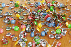 Office colored paper clips and drawing pins scattered on a table Royalty Free Stock Photography