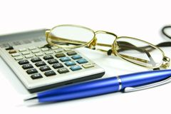 Office concept. Business / office concept shot, blue pen and a calculator with a pair of glasses stock photos