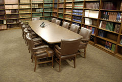Office Conference Room. Conference room table with several leather chairs and shelves of books stock photography