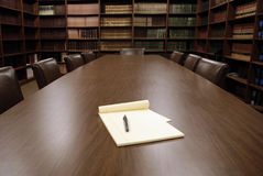 Office Conference Room. Conference room table with several leather chairs and shelves of books stock image