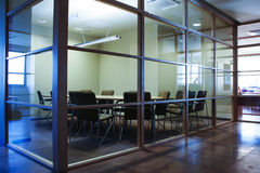 Office Conference Room with Glass Walls. An empty conference or meeting room with table and chairs surrounded by glass walls Royalty Free Stock Photography