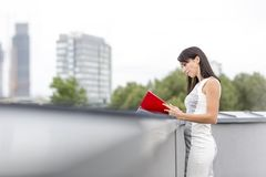 Confident businesswoman reading file at retaining wall on office terrace royalty free stock photos