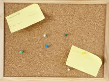 Office cork board with colored pins. A brown cork board with some pins and two post-it Stock Photo