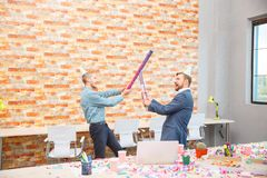 In the office at a corporate party, men are fooled with sticks from under confetti. The concept of a holiday, work Stock Photo