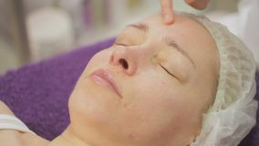 In the office of a cosmetologist, a woman is 40 years old on procedures. Ultrasonic face cleaning. Close-up stock footage